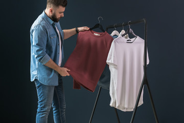 Hipster man dressed in denim shirt and jeans, stands indoors and looks at white T-shirt on clothes hanger in his hands.