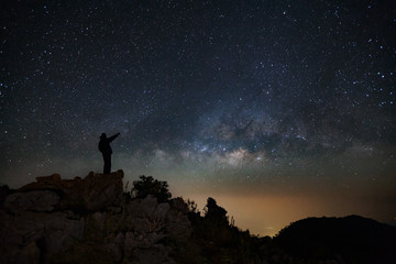 A Man is standing next to the milky way galaxy pointing on a bright star on Doi Luang Chiang Dao mountain, Long exposure photograph, with grain