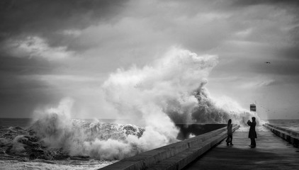 Crazy brave people on the pier near the lighthouse make photos during heavy storm against the backdrop of huge ocean waves. The Atlantic coast. Douro river mouth. Porto. Portugal. Europe.