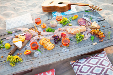 Aluminium Prints Picnic Picnic on the beach at sunset in boho style, food and drink concept