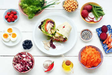 Healthy wrap sandwich on a plate. Making a wrap sandwich: flat bread, salad, carrot, cherry tomato, olives, eggs, chick peas, radish, cabbage, olive oil, soy sauce over white table. L