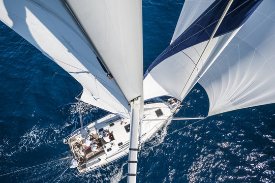 Sailing boat with spinnaker from top of the mast, motion blurred sea