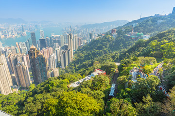 Aerial view of popular Peak Tram from Victoria Peak terrace, the highest peak of Hong Kong island, with panoramic city skyline in background. Sunny day.