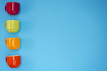 colorful four coffee cups on blue background.