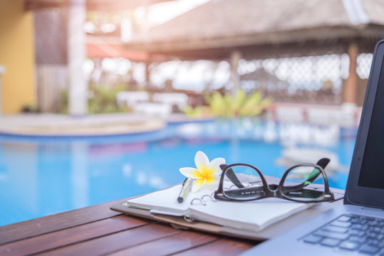 Work Relax, Laptop empty notebook pen and glasses on wooden table near swimming pool.