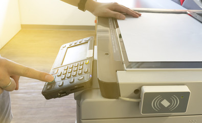 Man copying paper from Photocopier with access control for scanning key card sunlight from window Wall mural