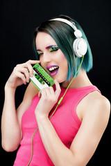 Portrait d'une jeune femme souriante, présentant une cassette audio dans sa main