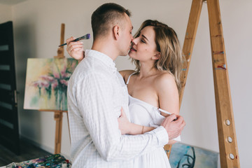 Happy couple flirting and painting picture.