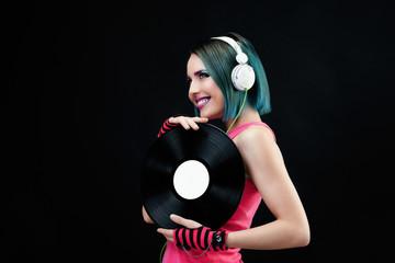 Portrait d'une jeune femme souriante, présentant un disque vinyle dans ses mains