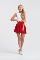 Girl with perfect body in red skirt on a white background