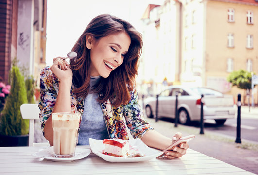 Happy young woman eating cake at outdoors cafe and read message on her smart phone
