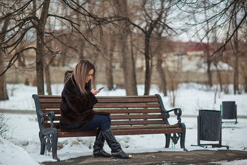 girl writes SMS sitting on a bench