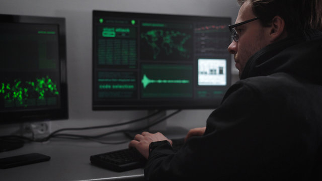 Computer room. On computers and desktop keyboard. The hacker tries to break into critical information. A man in a dark jacket and glasses gathers information using the keyboard is very concentrated.