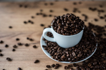 coffee cup filled by coffee beans on wooden background