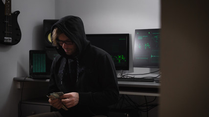 A hacker in the computer room. A man in a jacket with a hood, glasses and money in hands sitting in a chair. A guy with a happy mood to count money. Blonde man leer looking at the camera.