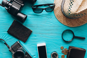 Top view of travel accessories set on wooden blue  background with copy space