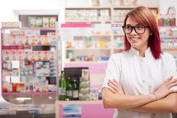 Smiling pharmacist in glasses in front of her desk