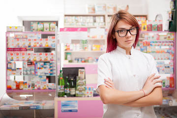 Pharmacist with glasses in front of her desk at work