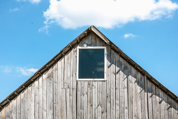 Unpainted old wooden shed with window