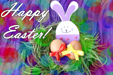 easter hand made decorated greeting card: yellow eggs and hand made festive plastic foam bunny in green grass twigs nest on purple background with inscription happy easter