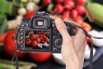 Male hand taking photo of Fresh, raw, organic vegetables on black background with digital DSLR camera. Cooking, Healthy eating concept.