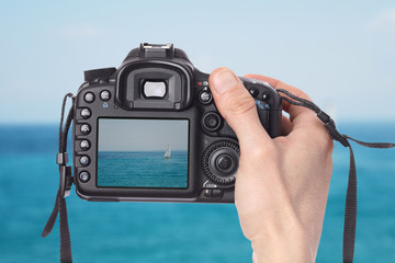 Male hand taking photo of a sailboat on the sea with digital DSLR camera.