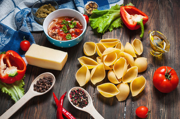 Raw Conchiglioni with minced meat and vegetables on dark wooden background