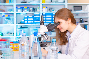 Women work in laboratory with microscope