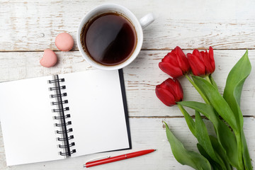 Red tulips, coffee cup and notebook over white wood table. Flat lay