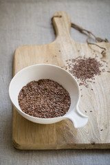 Flax seeds in bowl on wooden board on linen cloth background
