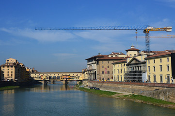 Beautiful view of Ponte Vecchio bridge over River Arno with crane for restoration, Florence, Italy
