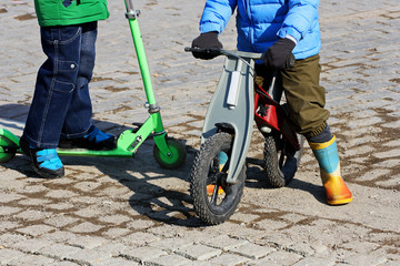 Children ride on a scooter and a balance bike.