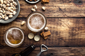 Papiers peints Biere, Cidre Two glasses of fresh beer and salty snacks on a brown wooden table, top view and space for text