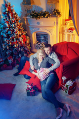 Pregnant with her husband at the fireplace. New Year's Eve is a planned pregnancy.