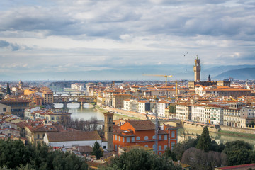 The cloudy sky over Florence. Birds over the river Arno and the Old Bridge