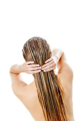 Photo of woman applying hair conditioner.