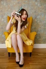 Young pin-up woman photographer with red lipstick holding camera
