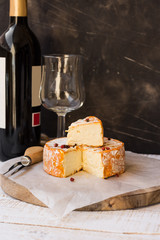 French munster cheese with orange rind, red pepper corns, cut off slice, fork,wine bottle and glass