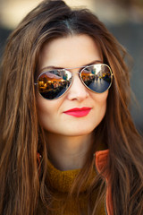 Outdoor portrait of young hispanic woman with curly hair in sunglasses with reflections of street