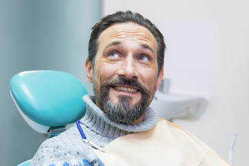 Man in dental chair smiling. Mature guy at the dentist. Quality dental services.