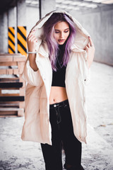 A beautiful girl with purple hair walks the streets of the city. Wearing a jacket, torn jeans. Stands in a hood in the parking lot