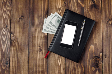 Business Concept - Top view of smartphone, watch, pen, notebook and money on wooden background.
