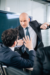 Businessman grabbing colleague by the tie during meeting