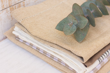 Stack of linen and cotton kitchen towels on white wood kitchen table, branch of silver dollar eucalyptus on top