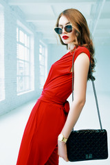 Indoor portrait of young beautiful fashionable woman posing in white interior with small quilted black leather bag. Model wearing stylish sunglasses, red overalls. Waist up. Female fashion concept.