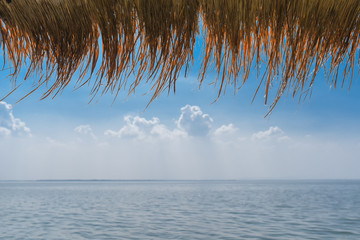 Thatched Roof with Sea and Sky in morning time