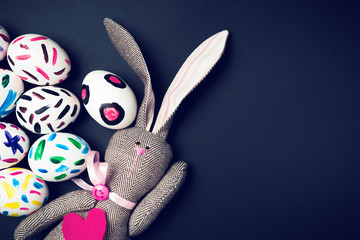 Easter bunny on a black background. Rabbit. Easter ideas. Easter eggs. Space for text. Image in trendy toning.