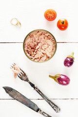 Tuna in a spring water in a can, piece of tuna on a fork, knife, cherry tomato and eggplants on a white table.
