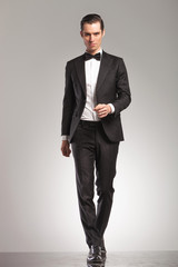 full body pictrue of a man in tuxedo walking forward