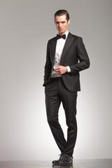 elegant business man in tuxedo standing with open coat